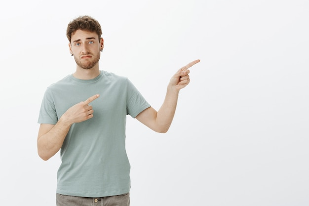 Indifferent unimpressed handsome man with bristle in earrings, pointing right with index fingers and smirking
