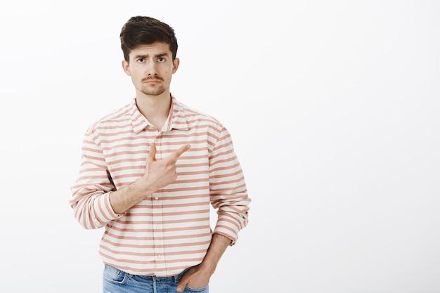 ひげと口ひげを持つ無関心で興味のない白人男性モデル、ポケットに手を握って、憂鬱な顔で右上隅を指す