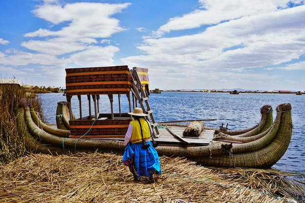 An indigenous woman heads to her totora boat on one of the floating uros islands, on the titicaca lake, near puno, perú.