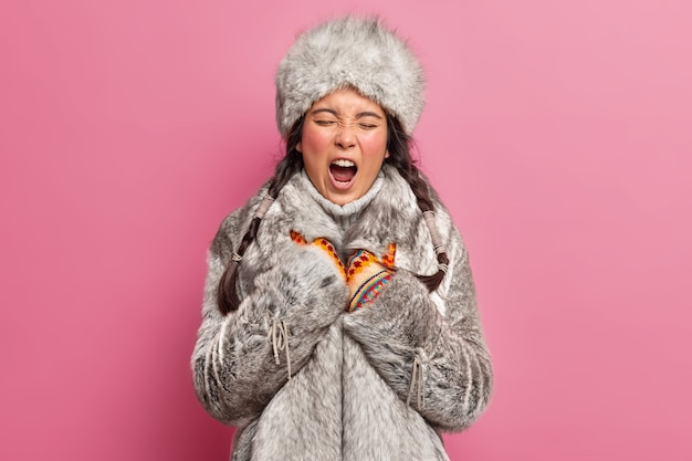 Indigenous woman yawns and has sleepy expression wears winter clothes lives at greenland poses against rosy wall