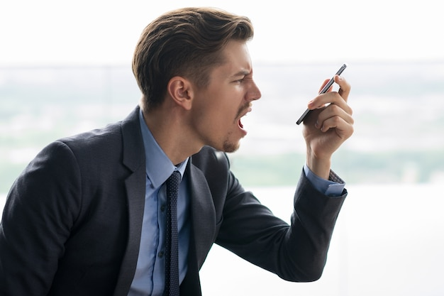 Indignant adult businessman angry at smartphone