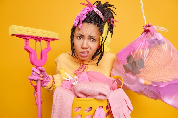 Indignant african american woman has dreadlocks poses with garbage
