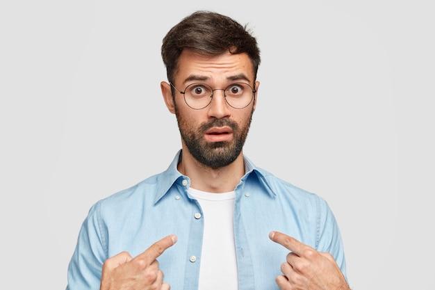 L'uomo barbuto indignato indica se stesso, scioccato da qualcosa