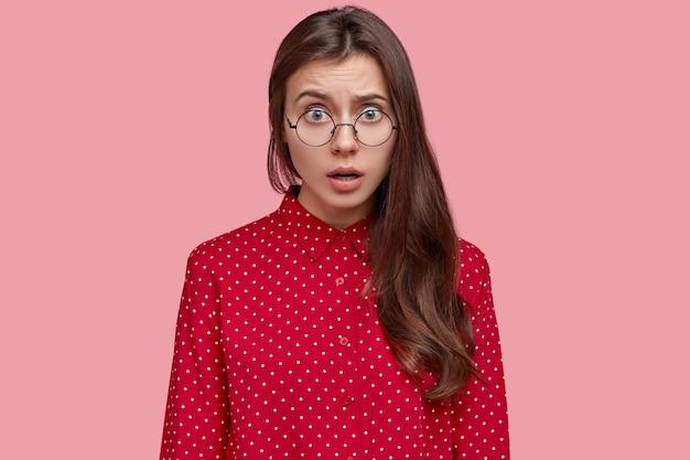 Возмущенная красивая молодая женщина чувствует обиду и непонимание, носит круглые очки и элегантную рубашку
