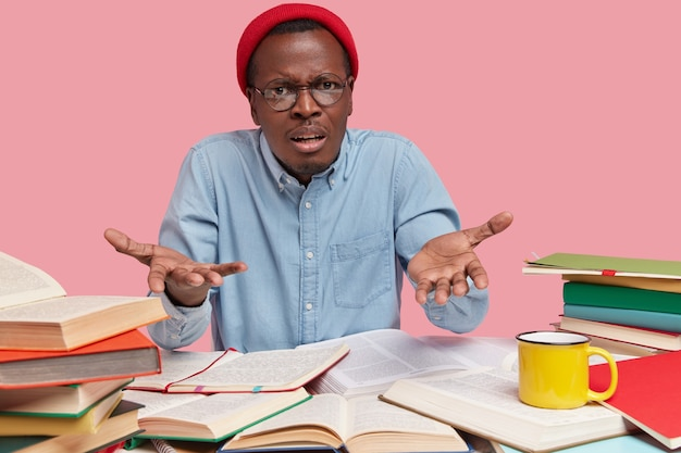 Indignant black teenage schoolboy gestures with bewilderment, wears red hat and formal shirt, asks what exactly he should do, reads textbooks