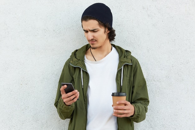 Indignant caucasian man looks with upset expression into smart phone, surfes social networks, connected to wireless internet