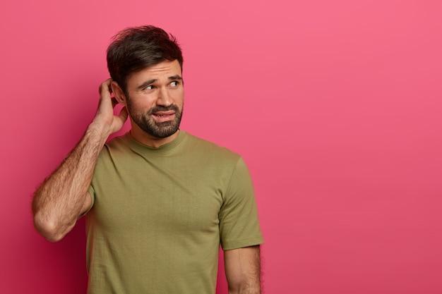 분개 혼란스러워하는 남자가 머리를 긁고 무언가를 결정하려고합니다.
