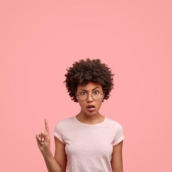 Возмущенная темнокожая кудрявая дама показывает указательным пальцем вверх