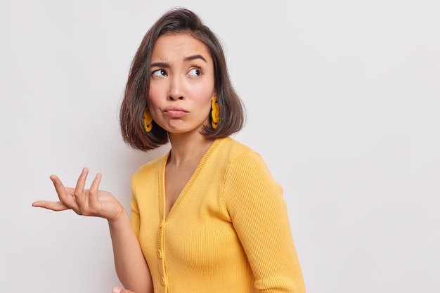 Indignant displeased asian woman concentrated away has sad expression raises hand with clueless look wears yellow jumper earrings poses against white wall copy space for text or promotion