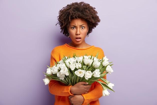 憤慨している不満のある女性は怒って見え、白い花を持って、オレンジ色のカジュアルジャンパーを着て、紫色の壁をモデルにして、否定的な感情を表現し、悪いニュースを聞きます。チューリップを持つ女性
