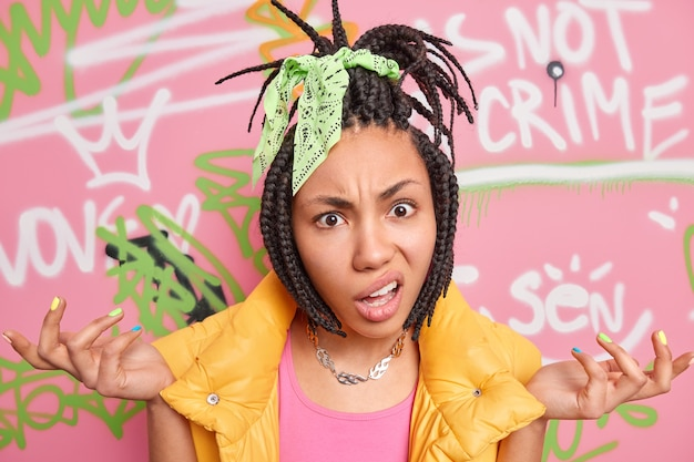 Indignant hipster girl has dreadlocks spreads palms says so what dressed in stylish clothes poses against colorful graffiti wall painted with aerosol spray