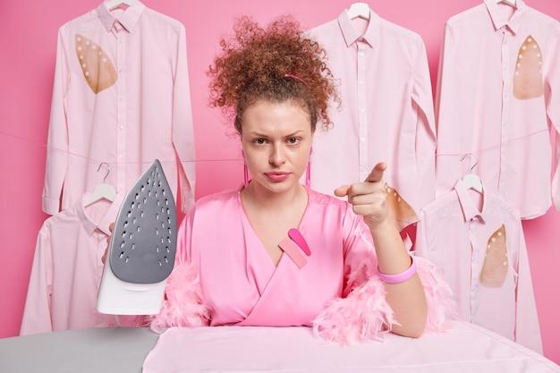Casalinga indignata con i capelli ricci pettinati punti e rimproveri che indossi vestaglia tiene ferro da stiro a vapore impegnato a stirare vestiti per la famiglia. il lavoratore della lavanderia ha un'espressione arrabbiata