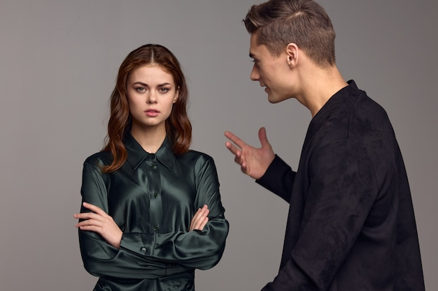 An indignant man in a black jacket gestures with his hands and looks at the woman. high quality photo