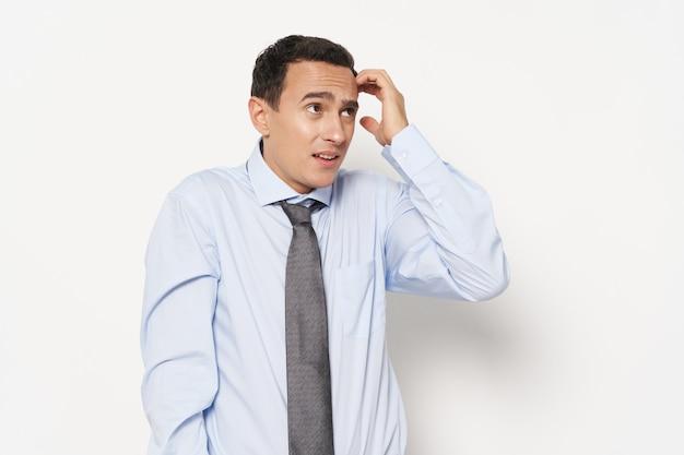 분개한 남자는 손과 가벼운 셔츠 넥타이 모델로 머리를 만진다