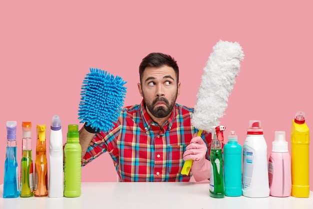 Indignant puzzled man with dark stubble holds mop and brush, dressed in checkered shirt, focused upwards, surrounded with cleaning detergents