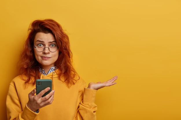 Indignant puzzled redhead woman raises palm, thinks what to answer on received message, holds mobile phone, wears round spectacles and hoodie, models over yellow wall with blank space right.