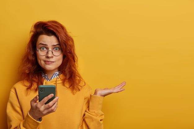Donna rossa indignata perplessa alza il palmo della mano, pensa a cosa rispondere al messaggio ricevuto, tiene in mano il cellulare, indossa occhiali rotondi e felpa con cappuccio, modelle sul muro giallo con uno spazio vuoto a destra.