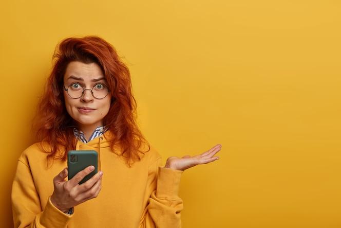 憤慨した困惑した赤毛の女性は、手のひらを上げ、受信したメッセージで何に答えるかを考え、携帯電話を持ち、丸い眼鏡とパーカーを着て、黄色い壁にモデルを置き、空白を右に置きます。