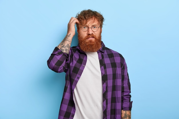 Indignant puzzled stylish ginger guy posing against the blue wall