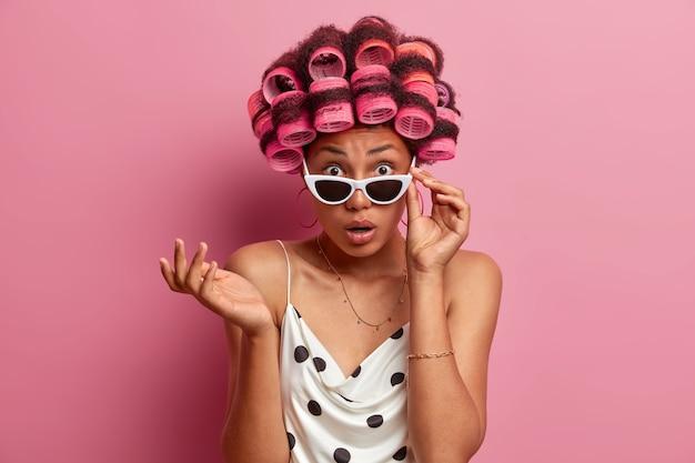 憤慨した困惑した女性はショックで見つめ、サングラスを握り、目を信じることができず、スタイリッシュなサングラスをかけ、ヘアローラーで髪型を作り、カジュアルな服を着て、屋内に立つ