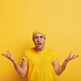 분개 한 어리둥절한 청년은 성가심으로 팔을 들고 의심스럽고 어려운 상황에 직면하고 숨을 참으며 노란색 모자와 캐주얼 티셔츠를 입습니다.
