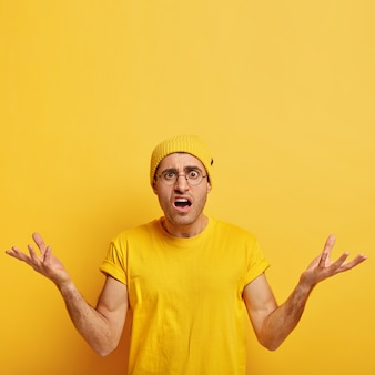 Indignant puzzled young man raises arms with annoyance, feels doubtful, faces difficult situation, holds breath, wears yellow headgear and casual t shirt