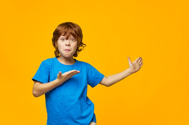 An indignant red-haired boy shows with his hand to the side