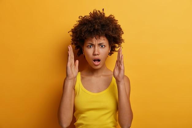 憤慨したショックを受けた女性が手で大きなサイズを作る