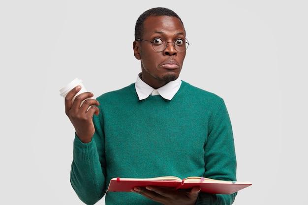 Возмущенный, удивленный темнокожий молодой ученый держит раскрытую книгу, несет ароматный кофе на вынос, носит круглые очки.