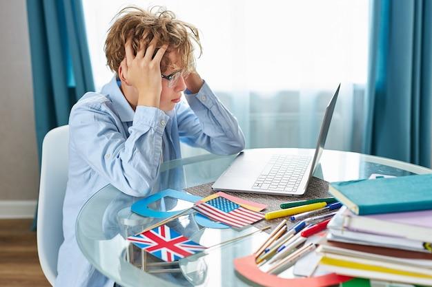 憤慨している疲れた少年は宿題をする方法を理解していません
