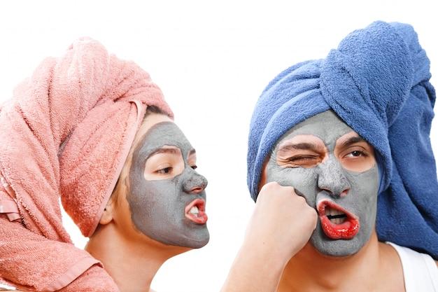 Возмущенная женщина бьет парня по лицу, маска для кожи мужчина и женщина, парень с женщиной делают маску для кожи вместе, смешная пара влюбленных, изолированное фото, эмоциональная половая роль Premium Фотографии
