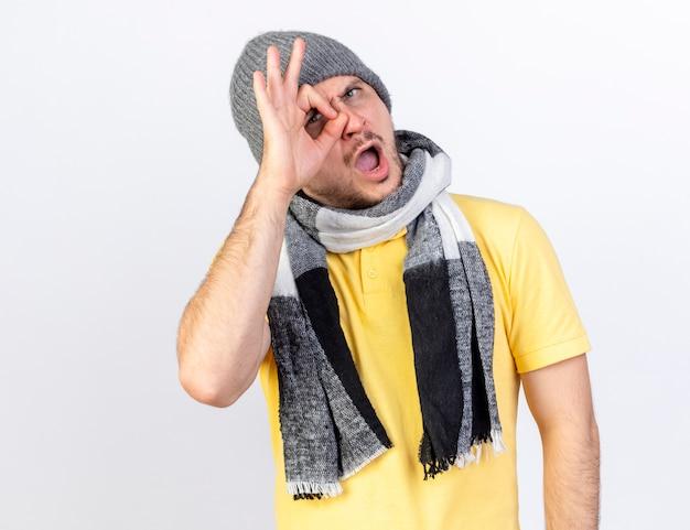 Возмущенный молодой блондин больной в зимней шапке и шарфе смотрит вперед сквозь пальцы, изолированные на белой стене