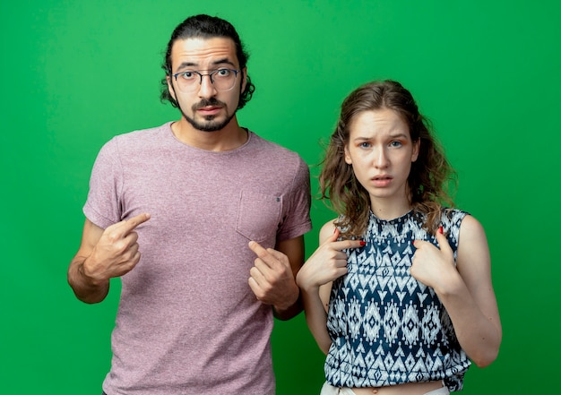 緑の壁の上に隣同士に立っている自分自身を指している憤慨している若いカップルの男性と女性
