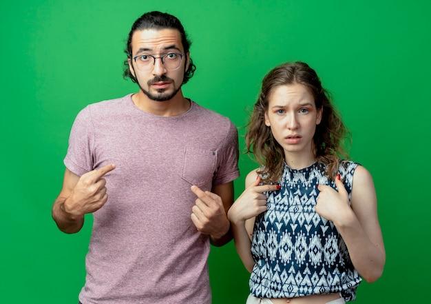 Giovane coppia indignata uomo e donna che punta a se stessi in piedi uno accanto all'altro sul muro verde