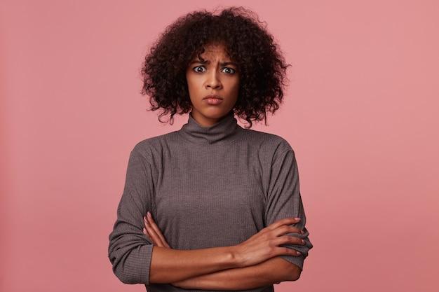 憤慨している若い巻き毛のブルネットの女性は、目を大きく開いて眉をひそめ、胸に手を組んだまま、黒い肌をしています。