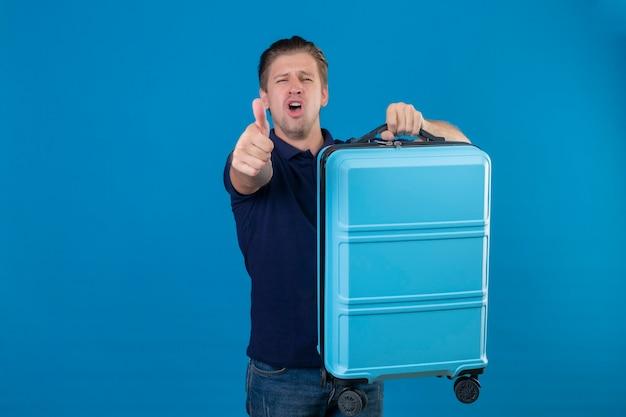 青いスペースの上に不満と欲求不満の立っているカメラにスーツケースの人差し指を保持している憤慨している若いハンサムな旅行者男