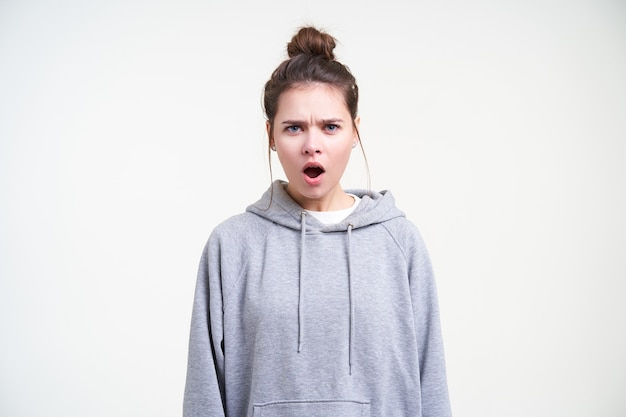 Giovane donna graziosa del brunette indignata con trucco naturale che aggrotta le sopracciglia mentre guarda con risentimento alla telecamera, in piedi su sfondo bianco