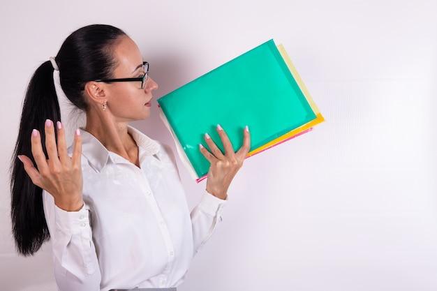 眼鏡をかけた憤慨した若い女性は彼女の手でカラーフォルダーを保持します