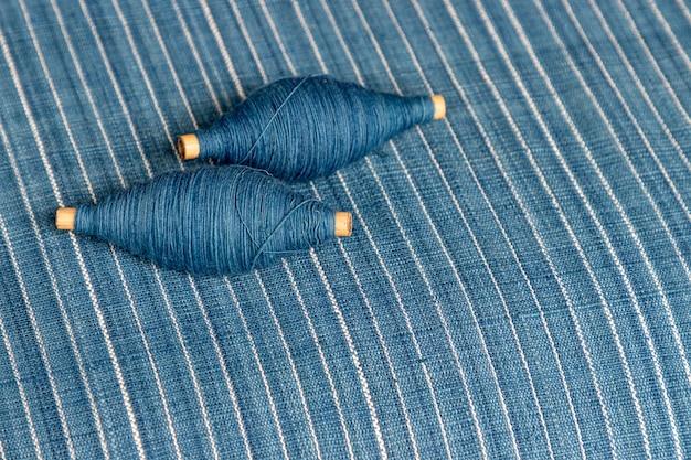Окрашенная в индиго пряжа в катушке и фон из ткани, окрашенной в индиго