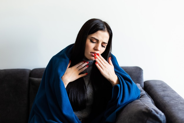 Indisposed sick woman feeling her temperature while resting on the sofa at home