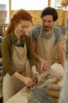 個人レッスン。プロのマスターの監督の下で初めて粘土の断片を転がす興奮した女の子の笑顔