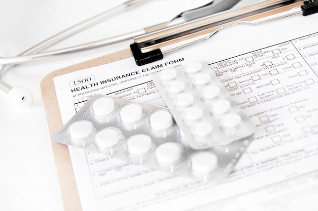 . individual medical health insurance policy with stethoscope and white pills