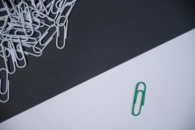 Индивидуальная скрепка выглядит иначе, как бизнес-значок. скрепки на черно-белом фоне.