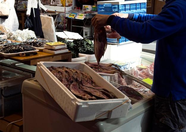 市場で新鮮な魚を探している個人