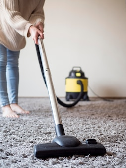 Individual vacuum cleaning the carpet