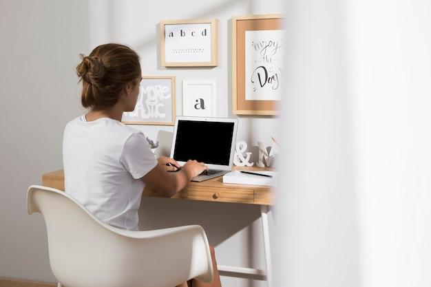 自宅でラップトップで作業する個人