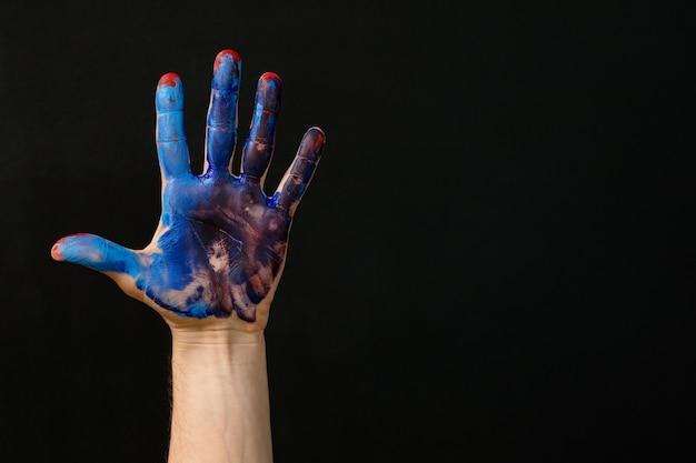 Индивидуальность и индивидуальность. рука замазана красно-синей краской. искусство хобби, образ жизни, занятие. творческая деятельность и терапия.