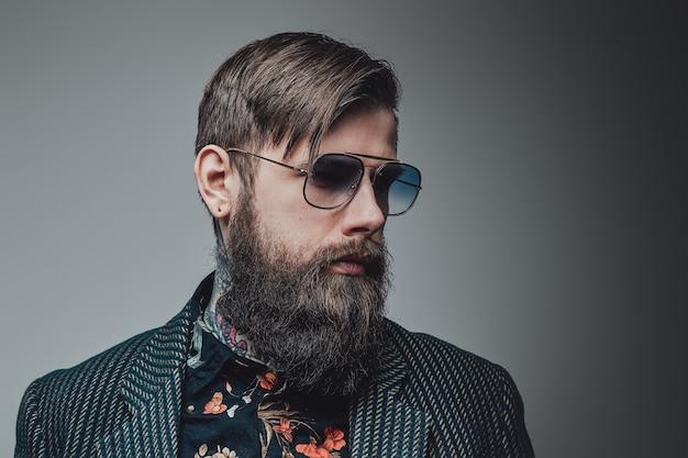 Индивидуальность хипстера в роскошном костюме. татуированный брутальный и элегантный мужчина позирует на сером фоне.
