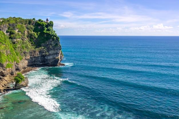 インドネシア。海の高くて岩だらけの海岸。日。崖の上にある小さな伝統的な寺院