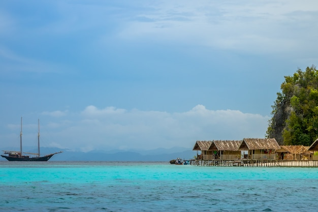 Индонезия. тропический остров, покрытый джунглями. пасмурный вечер. хижины на сваях в воде. яхта на якорной стоянке